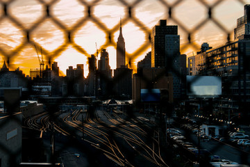 Empty train tracks glowing from behind a fence at sunset in New York.