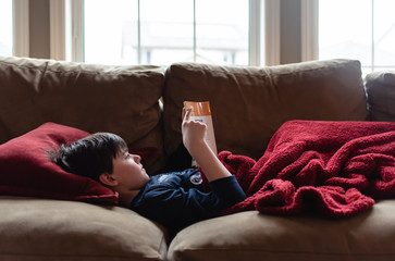Young boy reading a book on a sofa under a blanket.
