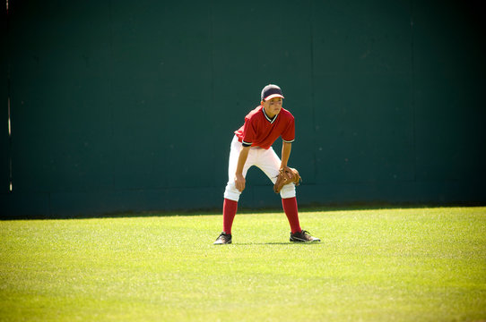 Boy in ready position in the outfield of a baseball field