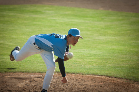 Pitcher in light blue and white jersey during wind up on a baseball field.
