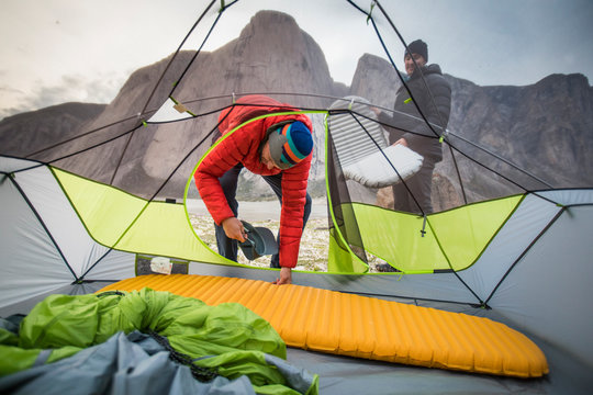 Two men set up sleeping pads in their tent during climbing trip.