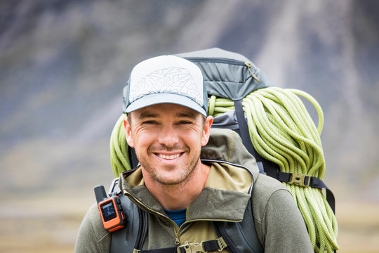Portrait of climber wearing backpack, rope and GPS communication tool