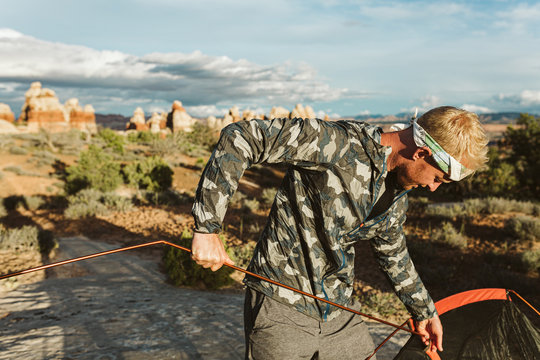 man wearing camo and headband sets up tent at sunset in the desert