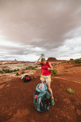 woman hiker eats apple and takes off her hat under stormy sky in utah