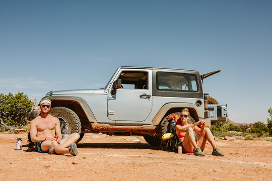 portrait of two straight faced hikers sitting in front of jeep