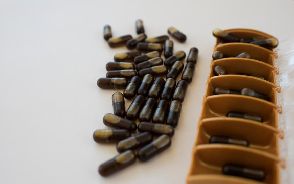 cbd capsules in a pill organiser on a white background