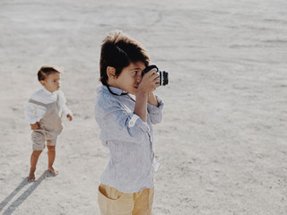 Boy taking picture with vintage camera with kid standing in background