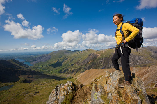 Woman overlooking Snowdonia National Park while standing on rock