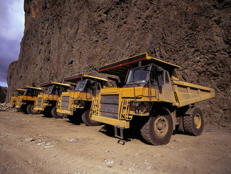 yellow dump trucks parked at side of a cliff