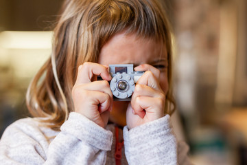 Blonde girl taking a picture with a Lego camera
