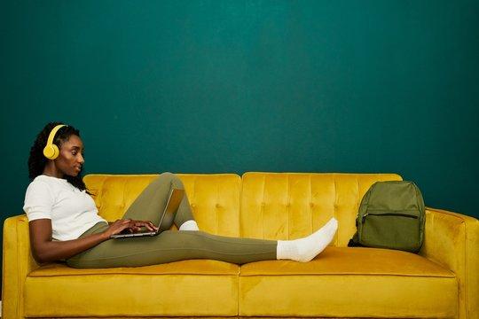 Afroamerican student laying at a yellow sofa front a dark green wall