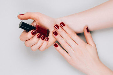 Photo sur cadre textile Manicure Beautiful dark red manicure with a bottle of nail polish in hands on a grey background. Procedures concept. Flat lay style.
