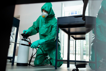 Careful man disinfecting the furniture with special chemicals stock photo