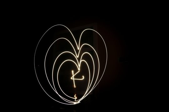 Close-up Of Illuminated Heart Shape Light Painting With Letter K Against Black Background