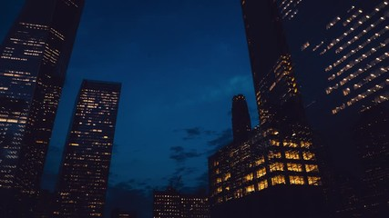 Fotomurales - Day to night transition timelapse of New York apartment buildings, below view of crowded city with lights turning on and off, fast paced modern night-scape in urban metropolis