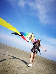 Tilt Image Of Woman With Colorful Kite Standing At Beach Against Blue Sky