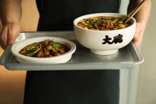 large bowls of noodles being brought out on tray by server