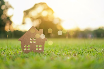 Fototapeta Closed up tiny home model on green grass with sunlight background.