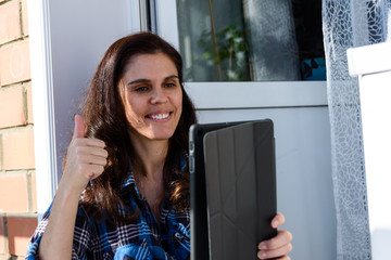 Brunette girl smiling looking at her tablet making a selfie or video call in balcony and says that everything will be fine with finger. Fun greeting online