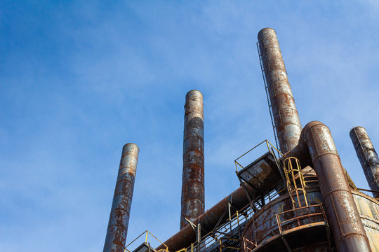 Tall, rusting smoke stacks silhouetted against a bright blue sky, abandoned industrial complex, copy space, horizontal aspect