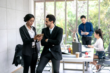 Business Man and Woman Working Together with Colleagues sitting in the background.
