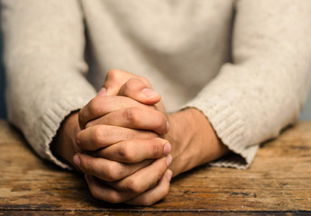 Image of praying hands. Praying hands of young man on a wooden desk Fotomurales