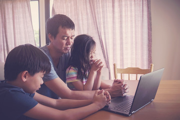 Children praying with father parent with laptop, family and kids worship online together at home, streaming online church service, social distancing, new normal  concept Fotomurales