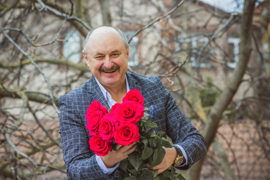 Older man in elegant jacket and roses, senior men lifestyle