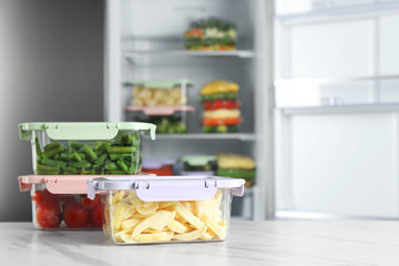 Containers with different frozen vegetables on white marble table near open refrigerator