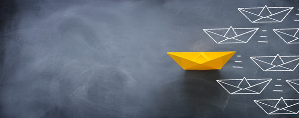 Leadership banner concept with paper boat on blackboard background. One leader ship leads other ships.