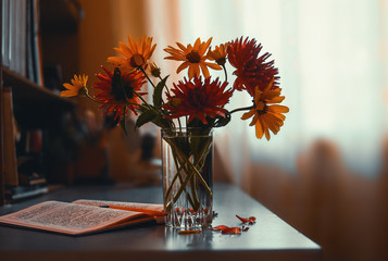 flowers in a vase are on the table, next to an opened notebook