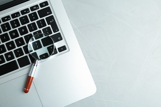 Magnifying glass and modern laptop on light grey table, space for text. Search concept