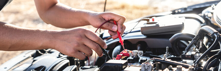 Mechanic repairman checking engine automotive in auto repair service and using digital multimeter testing battery to measure various values and analyze