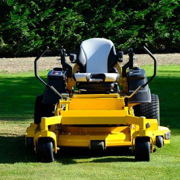 Lawn mower park by green grass field, zero turn Lawn mower.