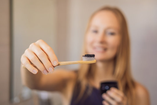 young woman brushing her teeth with a black tooth paste with active charcoal, and black tooth brush in her bathroom