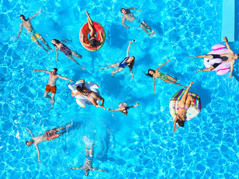 Aerial of friends having party in swimming pool with inflatable flamingo, swan, mattress. Happy young people relax at luxury resort on sunny day. View from above. Girls in bikini sunbathing in a sun.