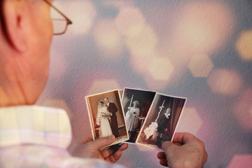 Wall Mural - old man's male hands hold old retro family photos in sepia color, genealogy concept, ancestral memory, family ties, childhood memories