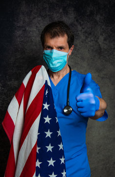 Doctor doing a thumb up hand sign, in blue hospital scrubs with face mask and stethoscope, with the American flag around his shoulders, against a dark studio background.