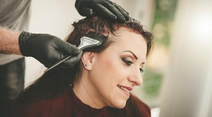 Foto auf Gartenposter Friseur Hairdresser coloring hair