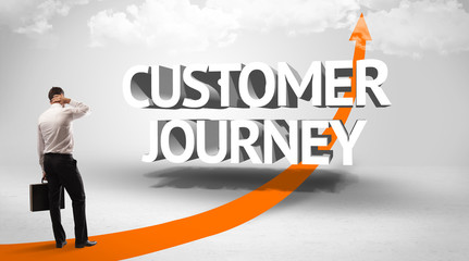 Rear view of a businessman standing in front of CUSTOMER JOURNEY inscription, successful business concept