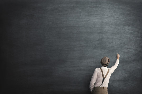 student writing on an empty blackboard with chalk
