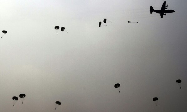 Silhouette Troops In Parachutes Dived From Airplane Against Sky At Dusk