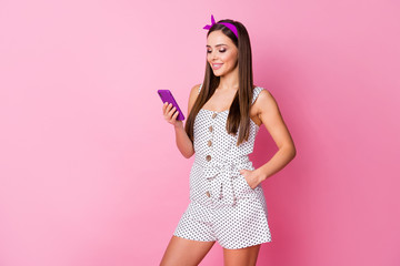 Photo of beautiful cheerful lady hold smart phone read boyfriend comment new picture post wear casual white dotted mini overall isolated pastel pink color background