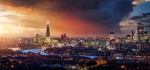 Fotomurales - Blick auf die beleuchtete Skyline von London während eines farbenfrohen Sonnenunterganges mit Wolken und Regen, Großbritannien