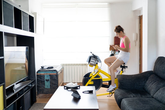 Young woman spinning at home and using mobile cell phone