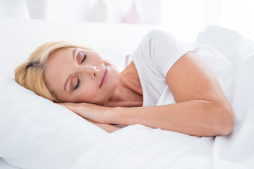 Fototapeta Close-up portrait of her she nice attractive lovely cute pretty calm aged woman lying in bed sleeping enjoying silence in modern light white interior room flat apartment indoors obraz