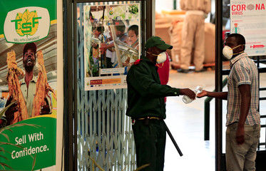 A security guard sanitizes a visitor at the start of the tobacco selling season, after the coronavirus disease (COVID-19) outbreak delayed the opening of auctions, in Harare