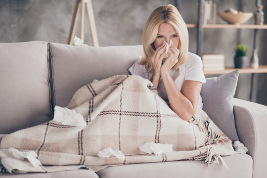 Portrait of her she nice attractive sick mature lady sitting on divan feeling bad blowing nose sneezing sick leave in modern industrial loft interior style living-room apartment