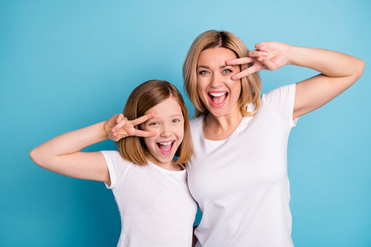 Photo of two people young beautiful mom lady small daughter good mood showing v-sing symbols near eyes saying hi friends wear casual white s-shirts isolated blue color background