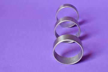 Metalowe srebrne kółka na fioletowym tle.